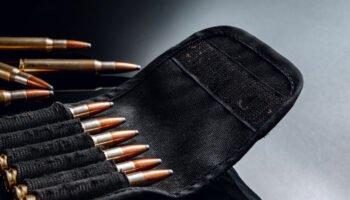 Rifle bullets or cartridges on black shiny close up